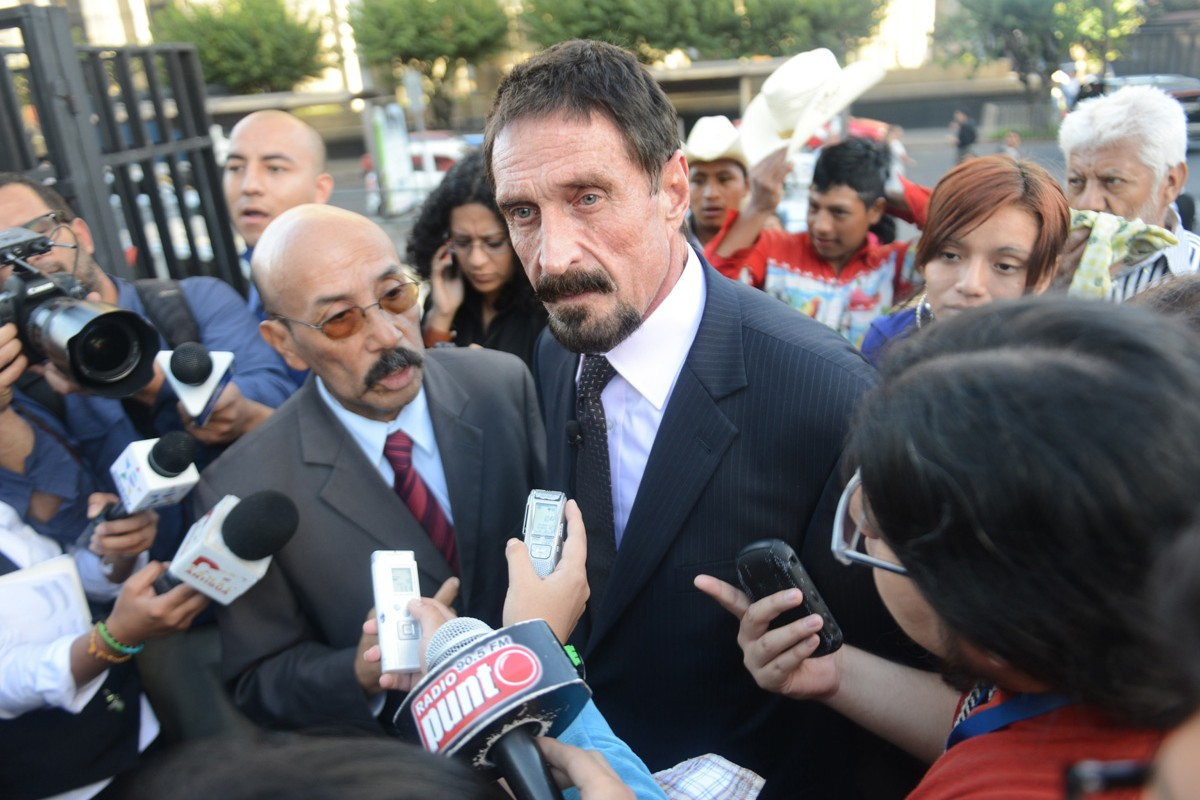 McAfee (with his lawyer, Telesforo Guerra, left) seeks political asylum in Guatemala following the November 2012 death of his neighbour in Belize.v