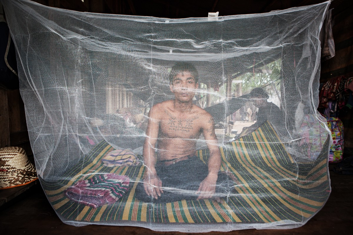 A villager sits beneath a mosquito net in Cambodia's Pailin province, which is ground zero for drug-resistant strains of malaria.