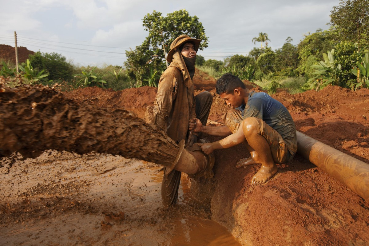 Workers repair a water pipe near a gem mine just outside Chanthaburi, Thailand.