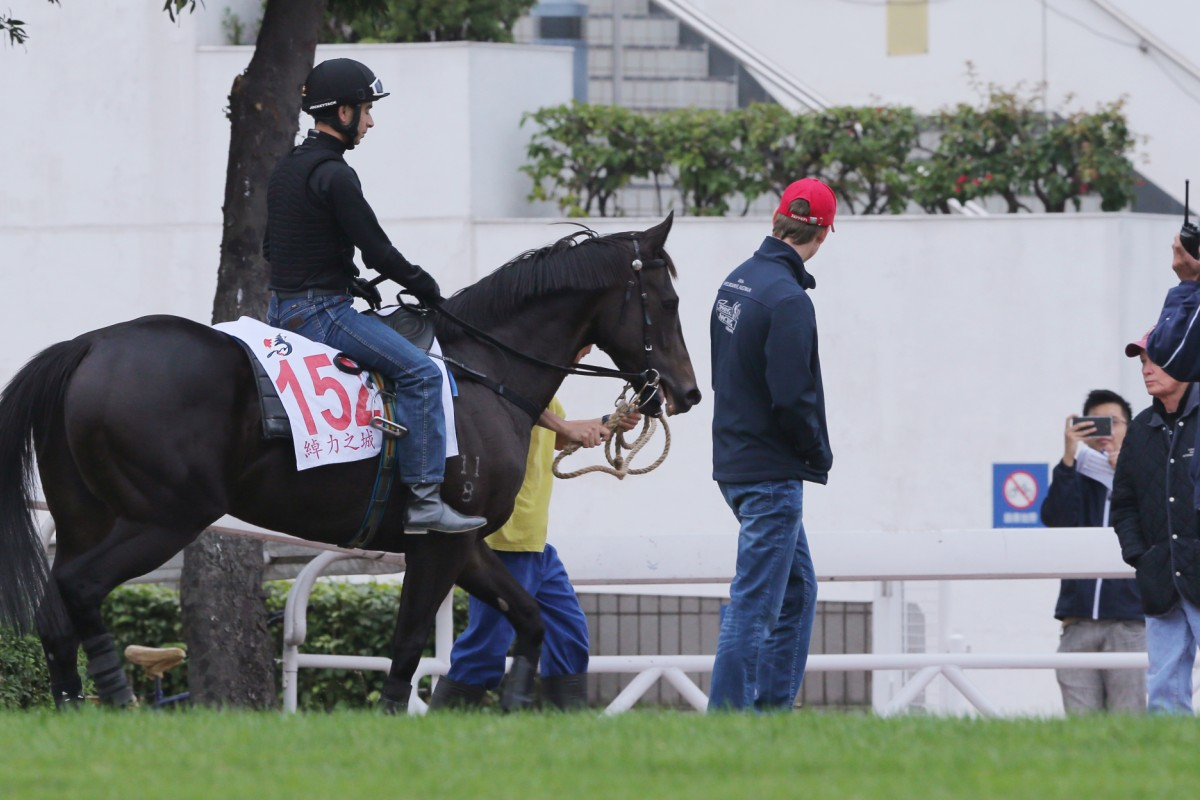 John Moore and son George watch on as Joao Moreira brings Sterling City back to the stables after his riverside gallop. Photo: Kenneth Chan