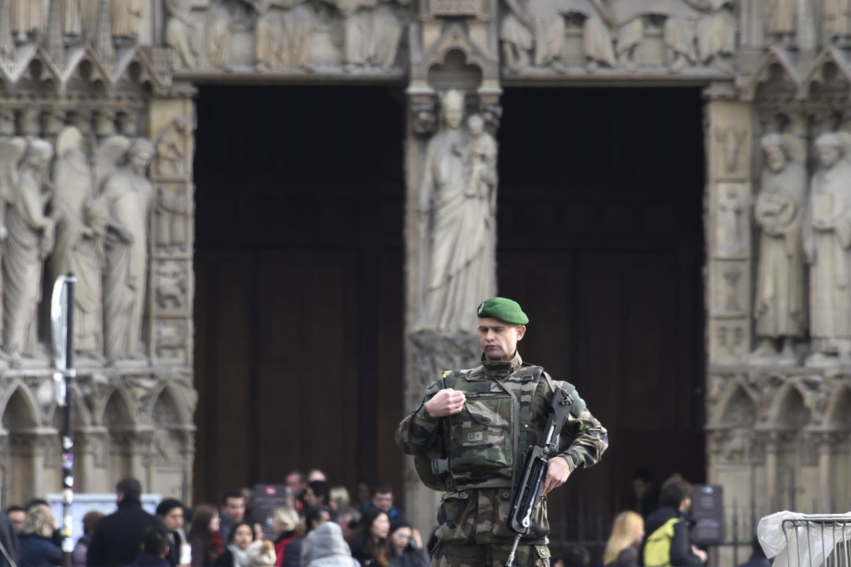 A soldier on patrol at the Notre-Dame de Paris cathedral on Christmas Eve. Photos: AFP; Corbis