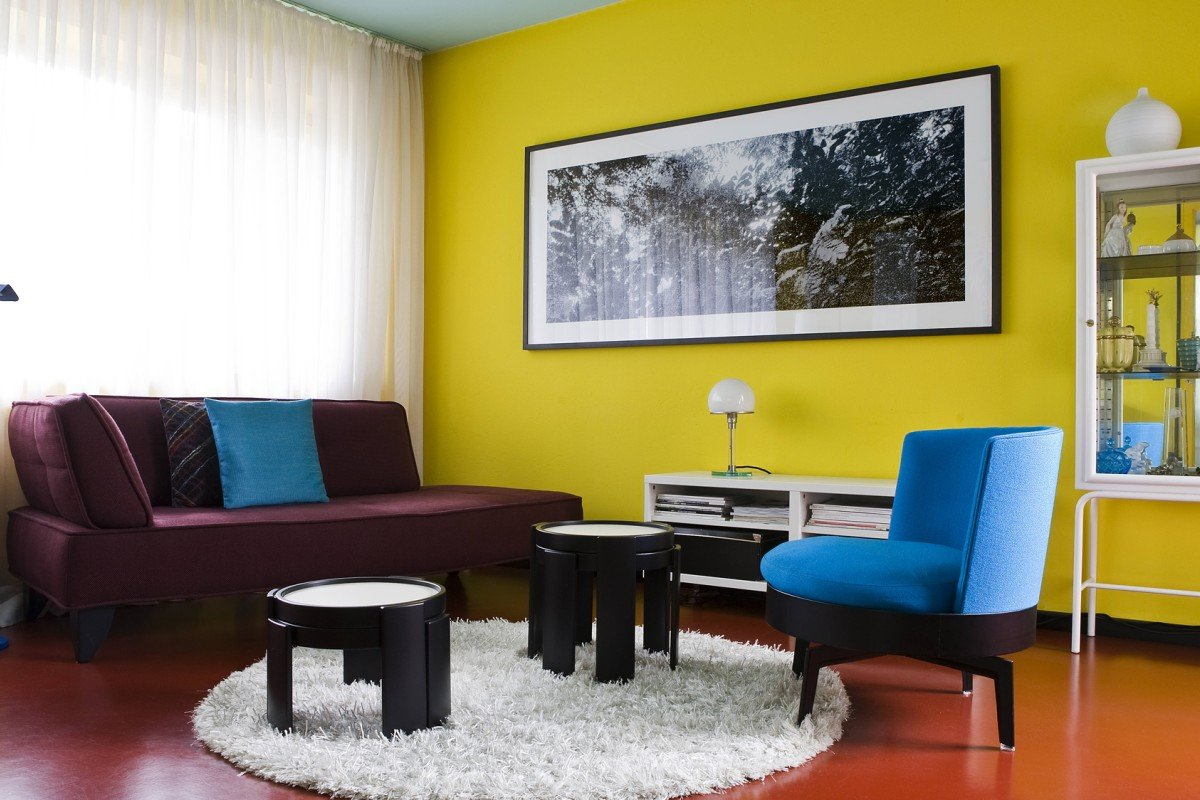 The living room features lemon yellow walls in stark contrast with a duck-egg blue ceiling and vermillion floor, not to mention the electric blue chairs and plum divan sofa. Photography: Helenio Barbetta