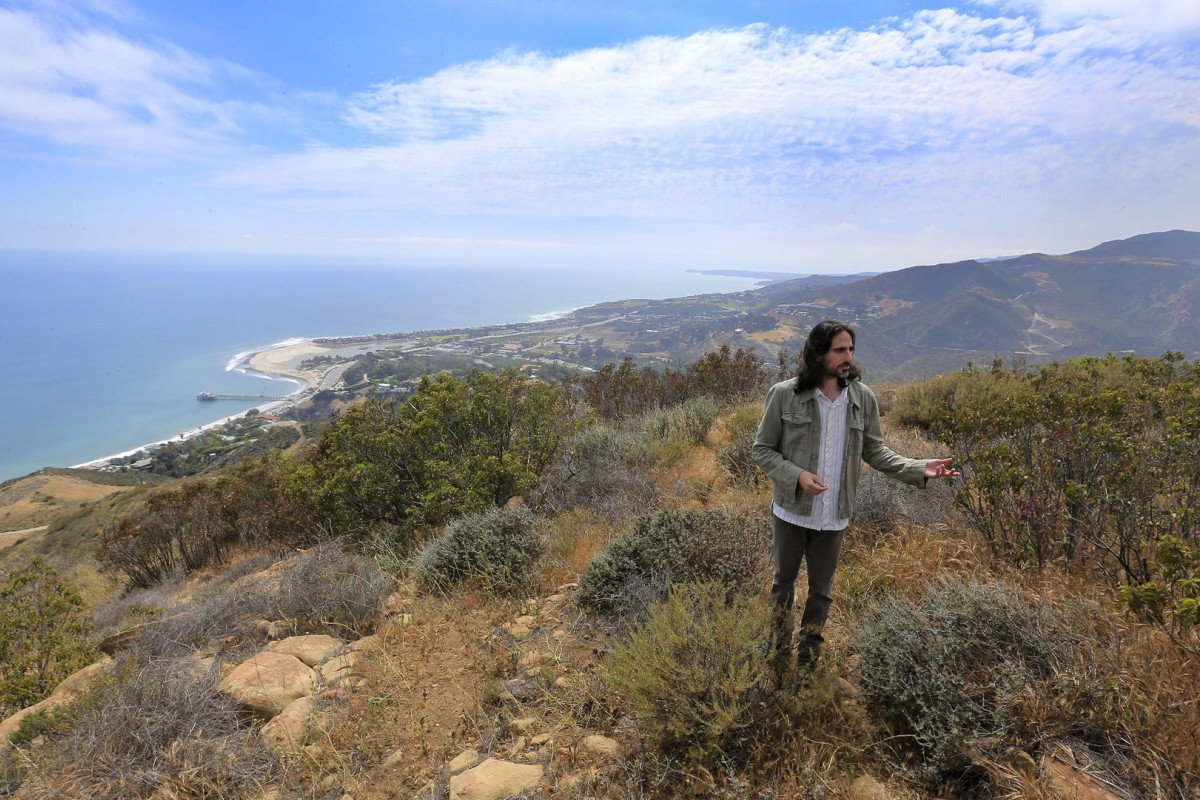 Project director Moses Hacmon on the hillside where The Edge planned to build a home. Photos: Los Angeles Times; AFP; Reuters