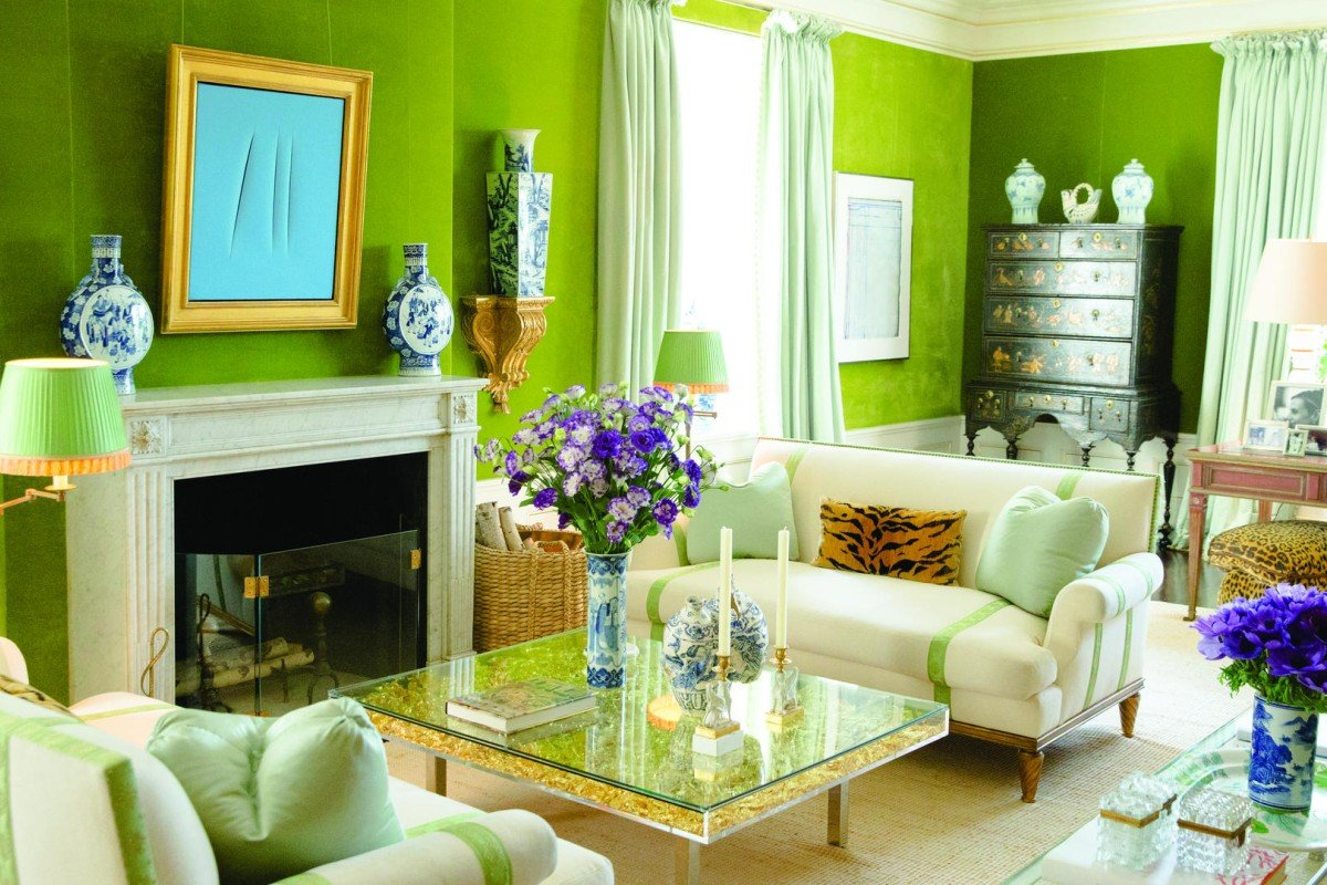 The living room features cool olive walls and pistachio curtains offset by striped cream furniture and a stunning coffee tablein gold.