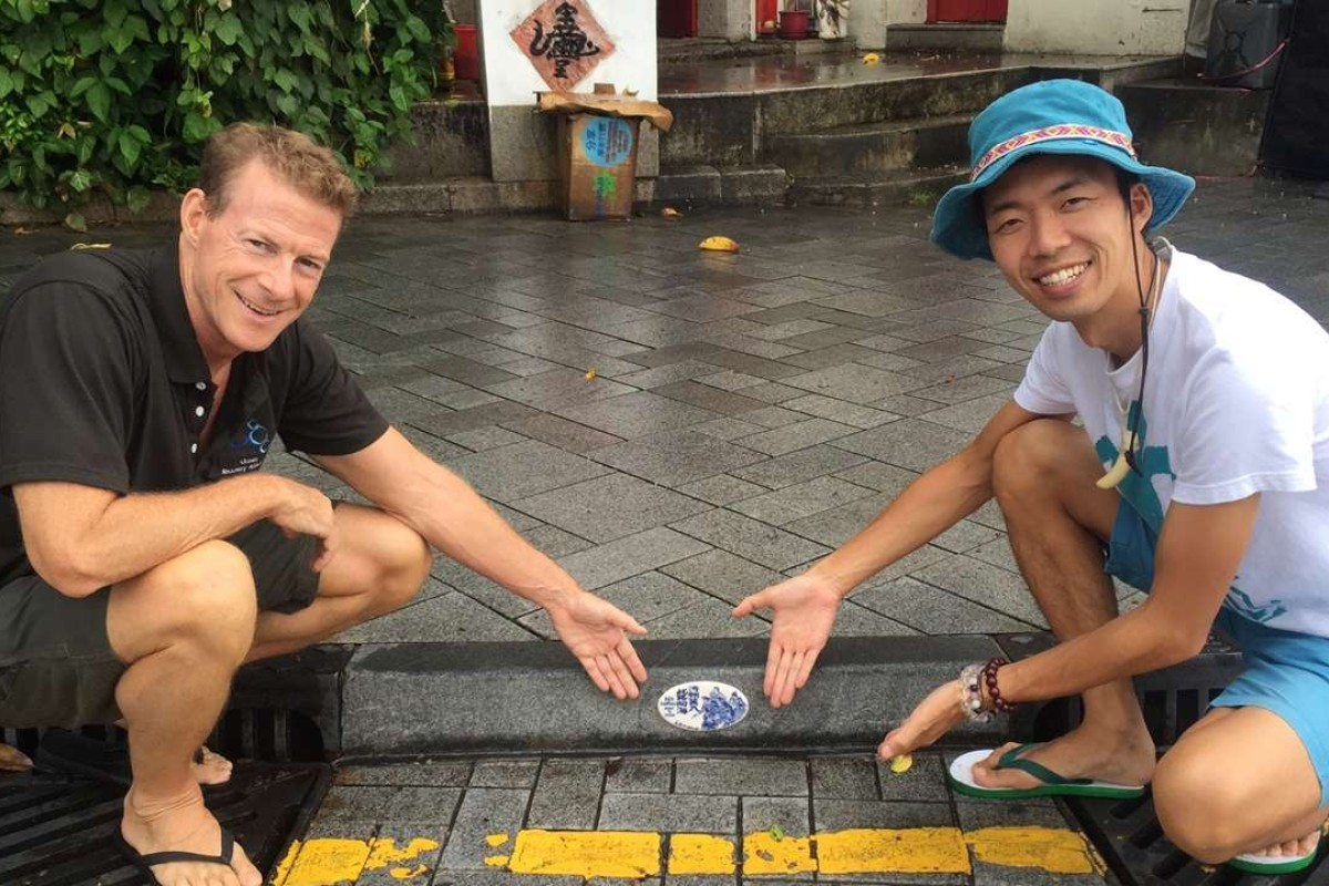 Doug Woodring and environmentalist Hiromasa Suzuki install a tile designed by Chen Huaxian, in Stanley.