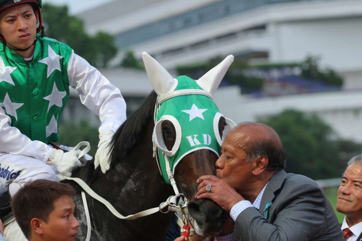 Kerm Din gives boom horse Pakistan Star a kiss, watched by jockey Matthew Chadwick and trainer Tony Cruz. Photo: Kenneth Chan