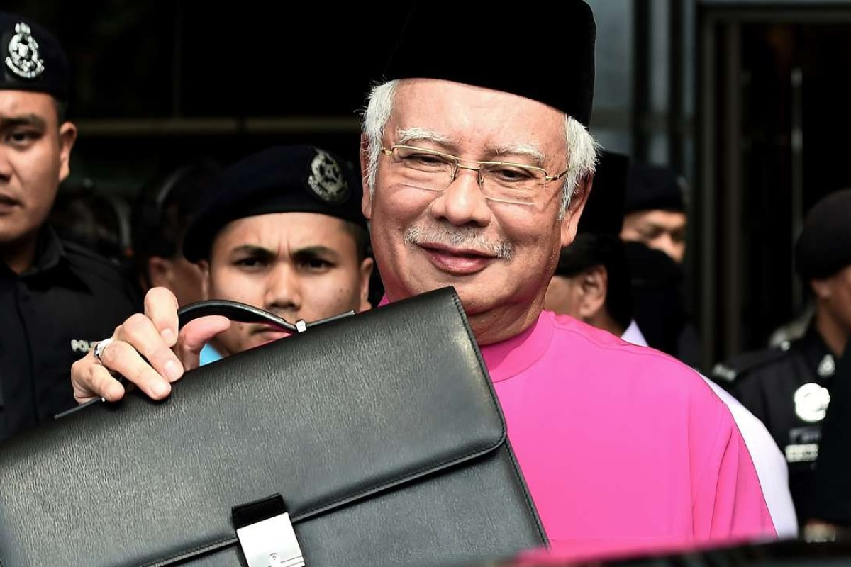 Malaysia's Prime Minister Najib Razak poses with his briefcase as he leaves to unveil the 2017 financial budget to Parliament House. Photo: AFP