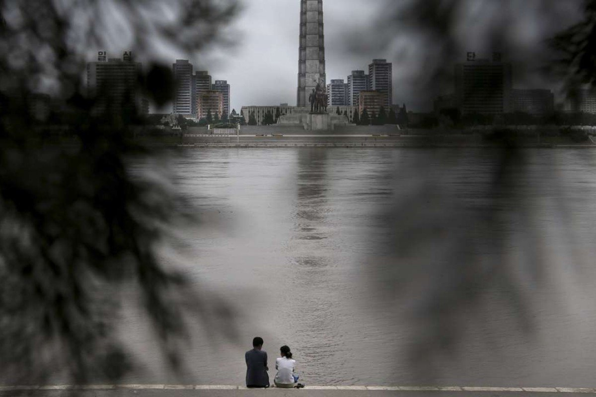 A North Korean couple sit by the river in Pyongyang. Adam Johnson wanted to know about the people who didn't defect, who strolled beside the river in Pyongyang and had picnics. Picture: AP