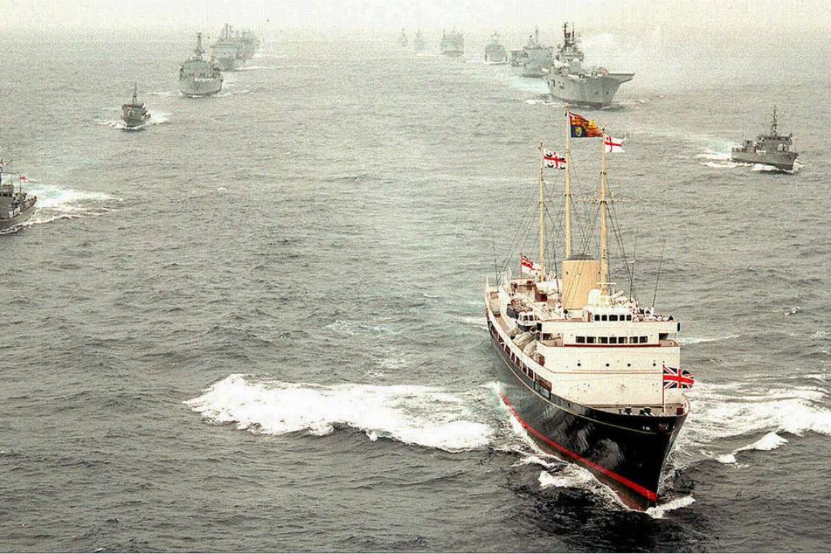 "The departing Royal Yacht Britannia, carrying the Prince of Wales and former governor Chris Patten, leads Royal Navy vessels in a ceremonial ""steam past"" to the south of Hong Kong, on July 1, 1997. Pictures: Reuters; SCMP"