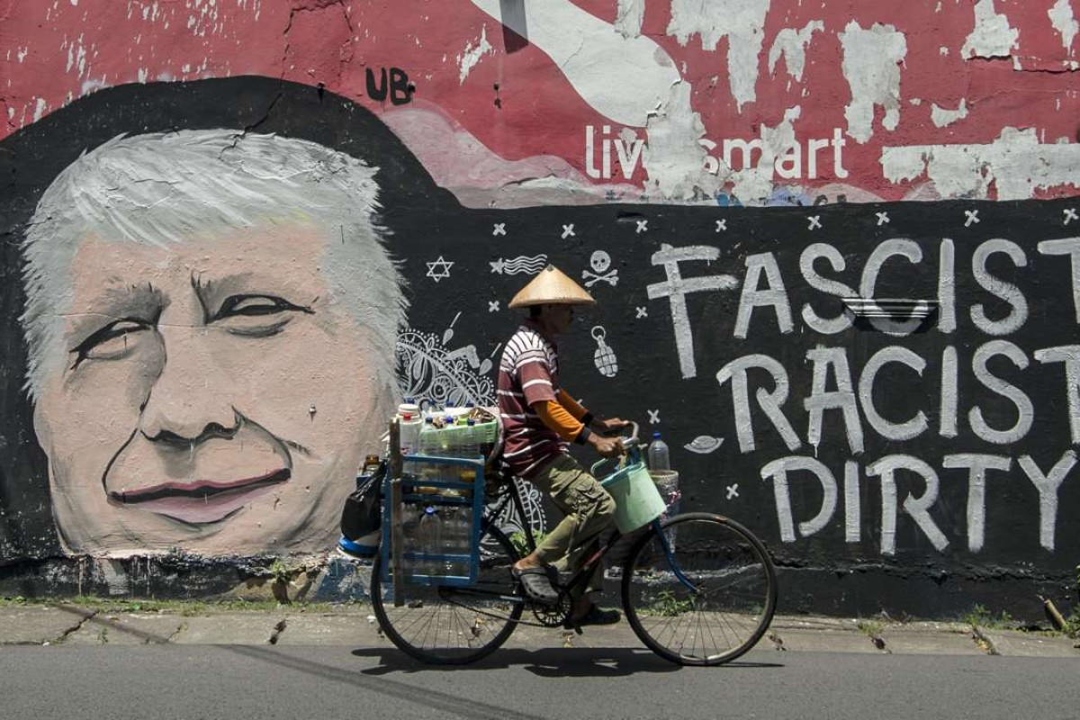 A man cycles past graffiti depicting US Republican presidential nominee Donald Trump, on a street in Surabaya, Indonesia's east Java. Photo: AFP