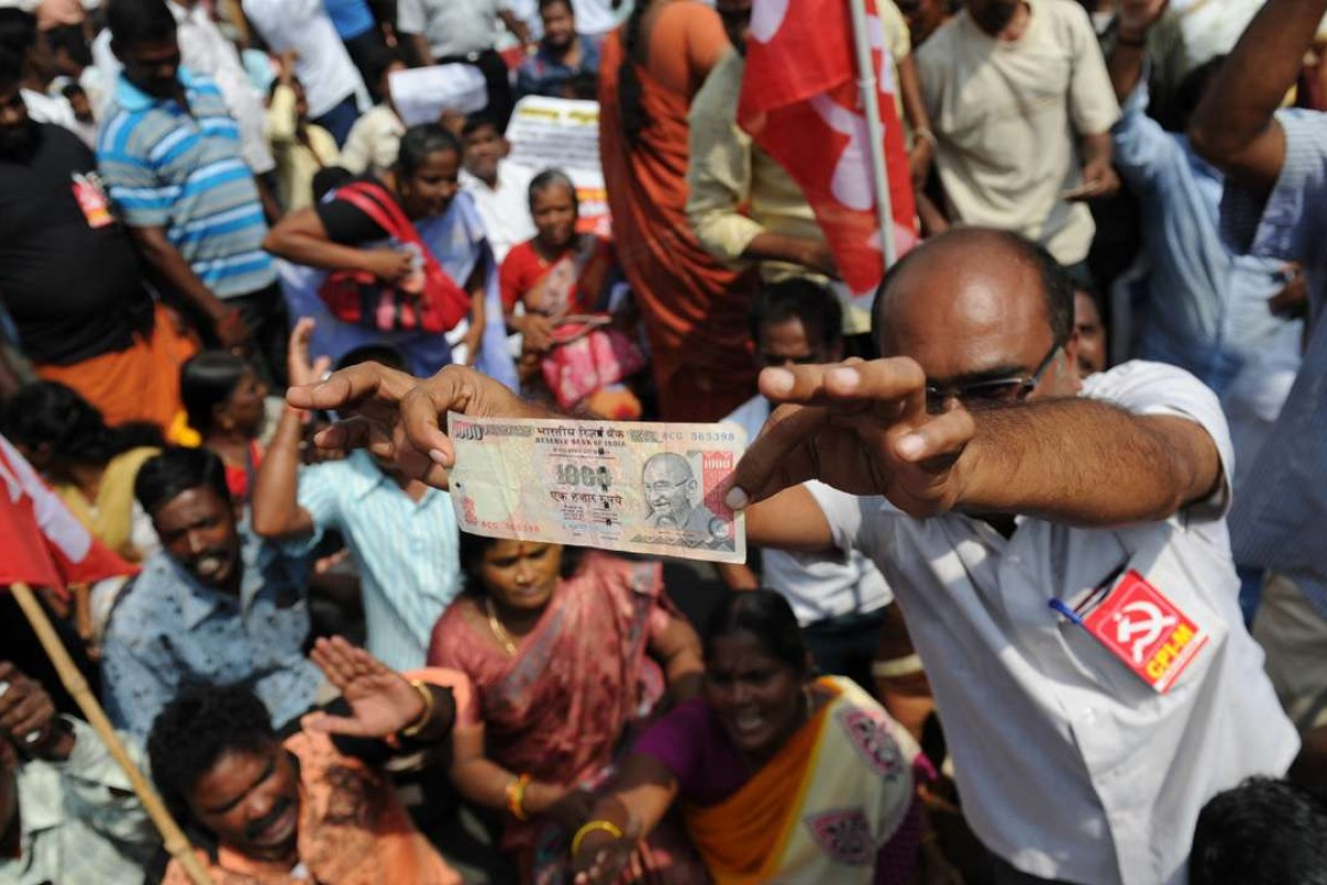 A member of the Communist Party of India displays a 1000 rupee note during a protest against Indian Prime Minister Narendra Modi and the withdrawal of the high-value banknotes from circulation. Photo: AFP/Arun Sankar