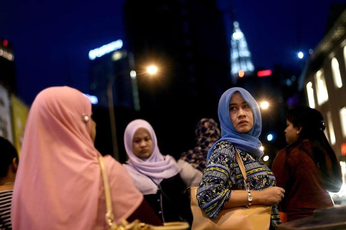 Malaysian women return from work in Kuala Lumpur. Malaysian PM Najib Razak has secured deals with China worth deals worth RM144 billion to the Malaysian economy. Photo: AFP