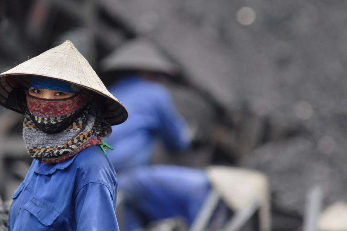 A miner takes a short break from sorting through coal at a mine in Uong Bi, northern Quang Ninh Province, Vietnam. The country has turned its back on its nuclear ambitions and has turned towards coal. Photo: EPA