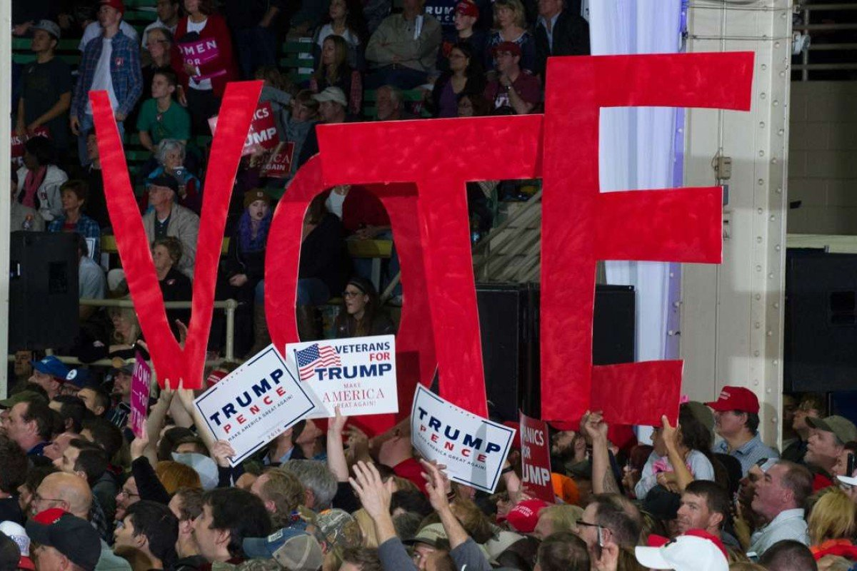 "Donald Trump supporers hold up giant letters spelling out the word ""vote"" in Denver, Colorado on November 5, 2016. Picture: AFP"