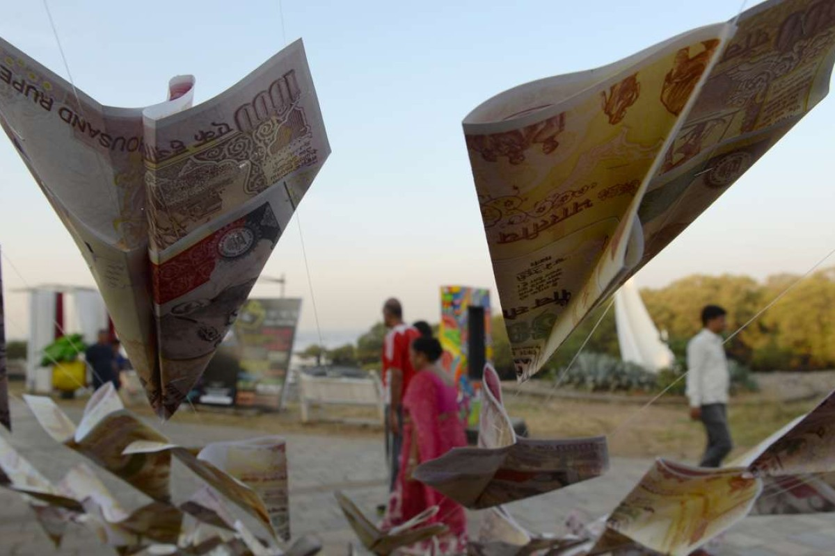 Indians walk past replica prints of the demonetised 500 and 1,000 rupee notes as part of a street art exhibition in Mumbai. Photo: AFP