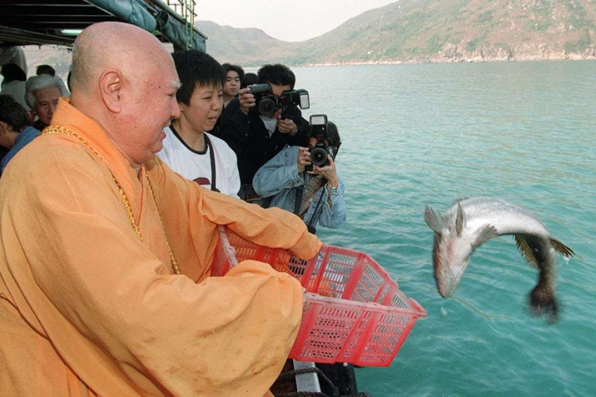 "Reverend Sik Wing-sing releases a fish off Sai Kung in a ""saving life"" ritual in 1997. The practice is widespread in the city. Picture: Robert Ng"