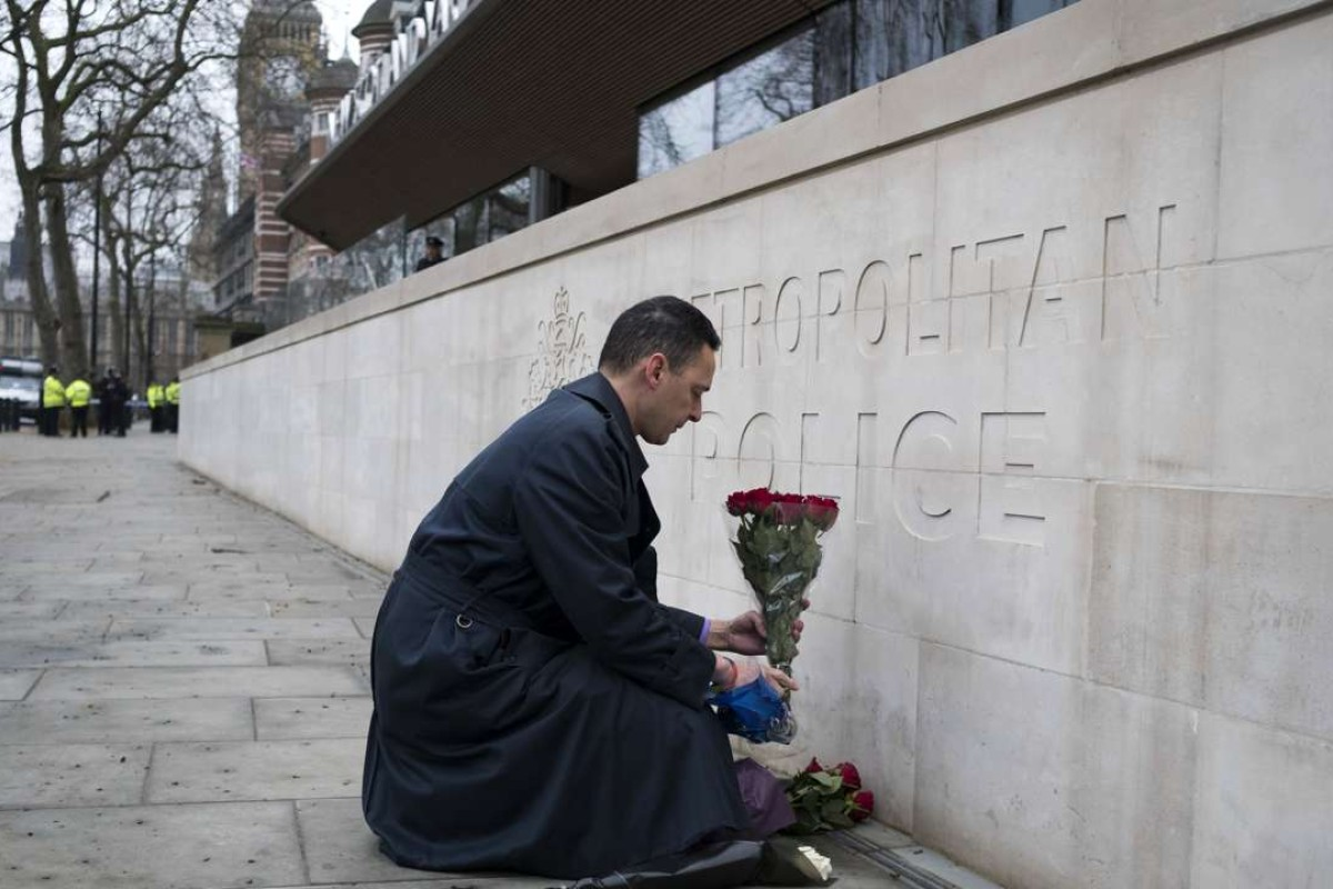 A man lays flowers outside New Scotland Yard in central London. Scotland Yard said police have made seven arrests in raids carried out over night in Birmingham, London and elsewhere after the terror attack in the Westminister Palace grounds and on Westminster Bridge that left three people dead, including the attacker. Photo: EPA