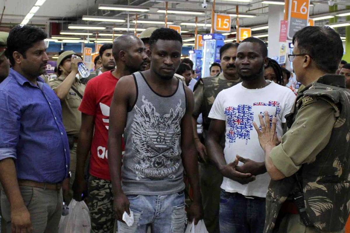 Indian police and onlookers surround African nationals at a shopping mall in Greater Noida on March 27. Hundreds of residents of an Indian city where a teenage boy died of a suspected drug overdose went on a violent rampage against Africans, using steel chairs to attack shoppers in a local mall. The riots broke out after New Delhi released five African students detained over the death. Photo: AFP