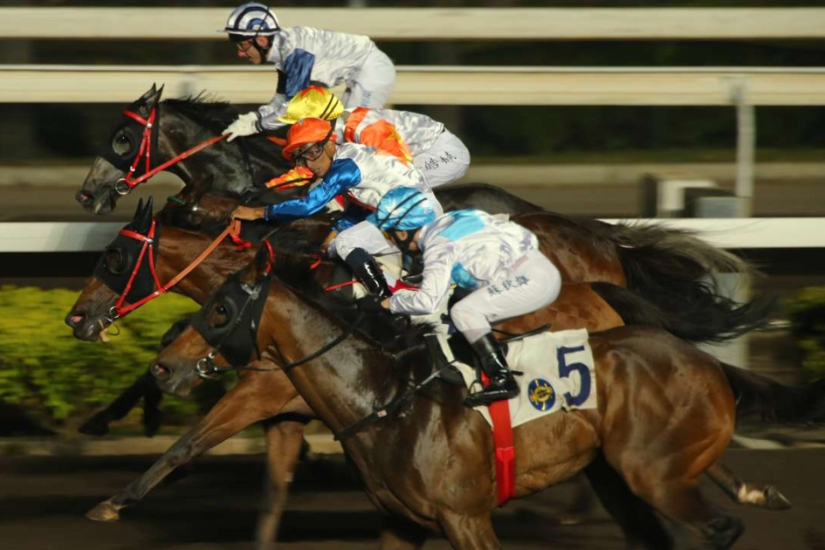 Ben So and Goldie Flanker (blue and white, outside) storm over the top to win at Sha Tin on Wednesday night. Photos: Kenneth Chan