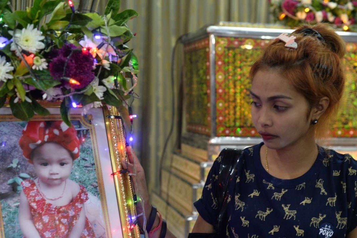 Jiranuch Trirat, mother of an 11-month-old girl killed by her father who broadcast the murder on Facebook, next to a picture of her daughter at a temple in Phuket. Photo: Reuters