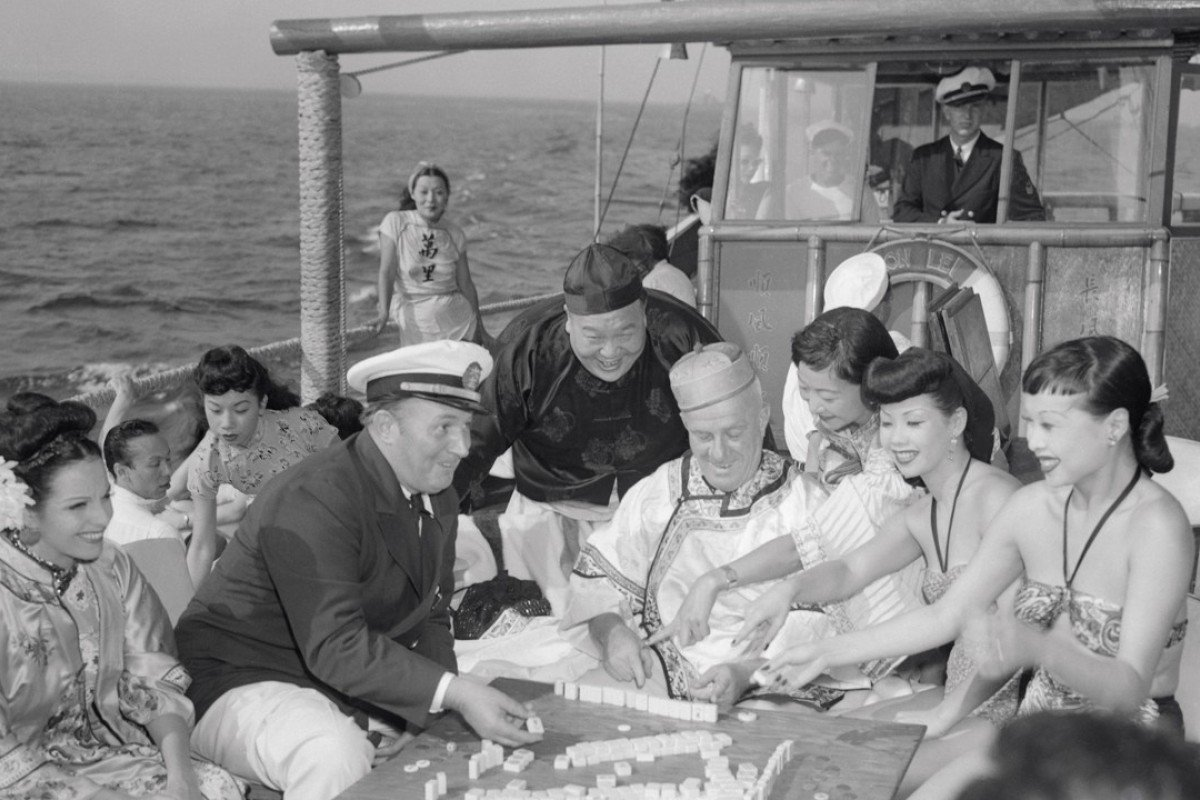 Robert Ripley (seated, in captain's hat) and his guests enjoy a game of mahjong aboard the Mon Lei. Picture: Getty Images