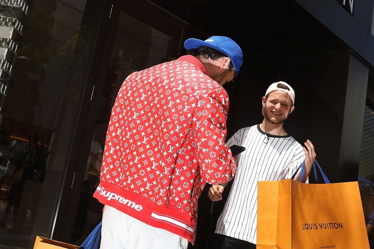 A shopper wears a new Supreme shirt as people flock to the Louis Vuitton store to purchase limited edition supreme and Louis Vuitton collaboration items on June 30, 2017 in Miami. Photo: AFP