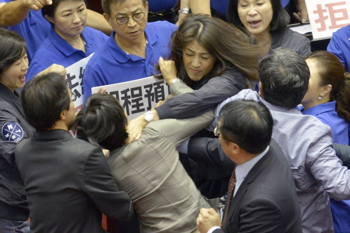 Taiwan's main opposition Kuomintang legislator Hsu Shu-hua, centre facing camera, brawls with ruling Democratic Progressive Party's Chu Yi-ying during a review of a major infrastructure project at the Parliament in Taipei. Photo: AFP