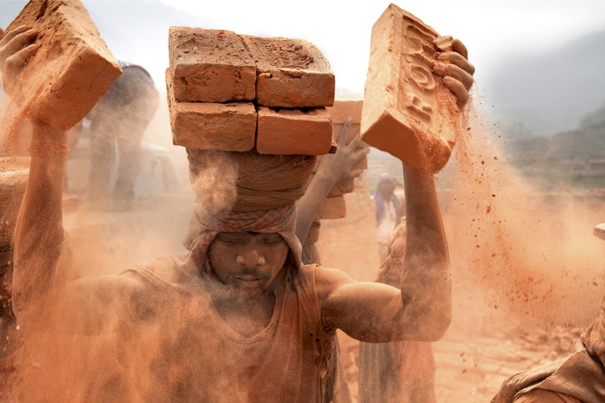 Stacking – Nepal: a brick kiln in Nepal. Each brick weighs about 2kg. The dust goes straight into the slaves' lungs. Picture: Lisa Kristine
