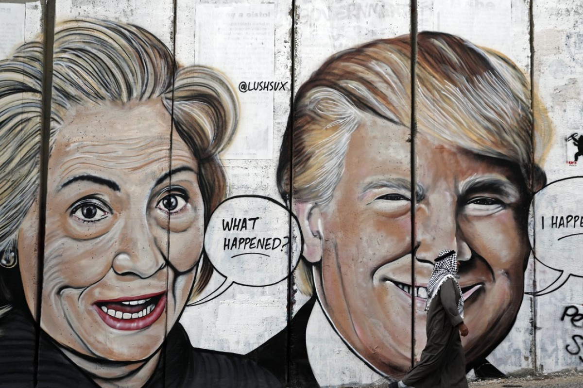 A Palestinian man walks past graffiti depicting US presidential candidate Hillary Clinton and US President Donald Trump on the controversial Israeli wall separating the West Bank town of Bethlehem from Jerusalem. Trump taking over as US leader was the year's biggest story. Picture: AFP