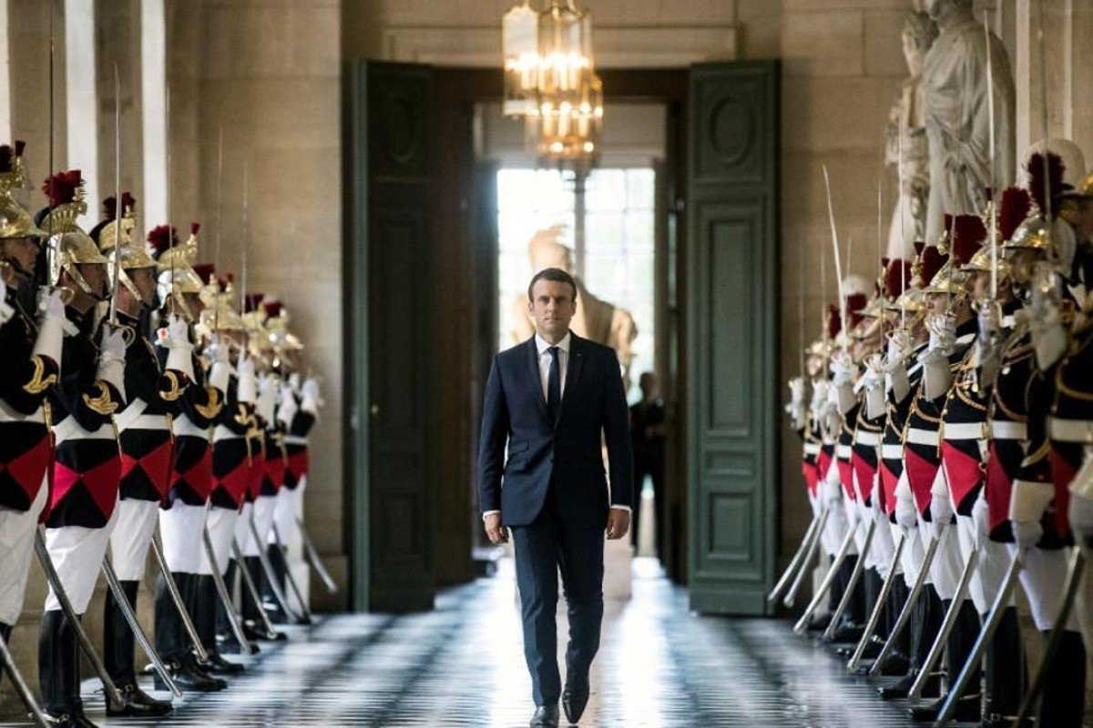 French President Emmanuel Macron walks through the Galerie des Bustes. Photo: REUTERS/Etienne Laurent