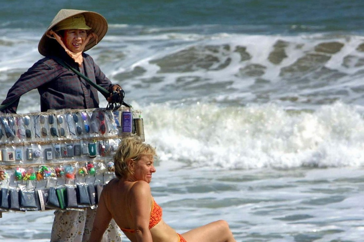 A vendor tries to sell sunglasses to a tourist in Nha Trang, Vietnam. Photo: AFP