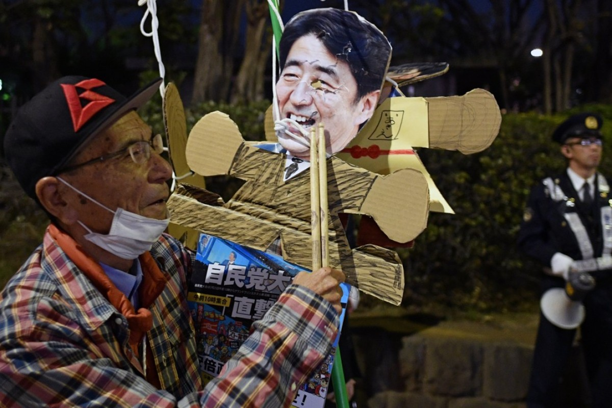A protester at the National Diet in Tokyo demands the resignation of Japanese Prime Minister Shinzo Abe. Photo: EPA