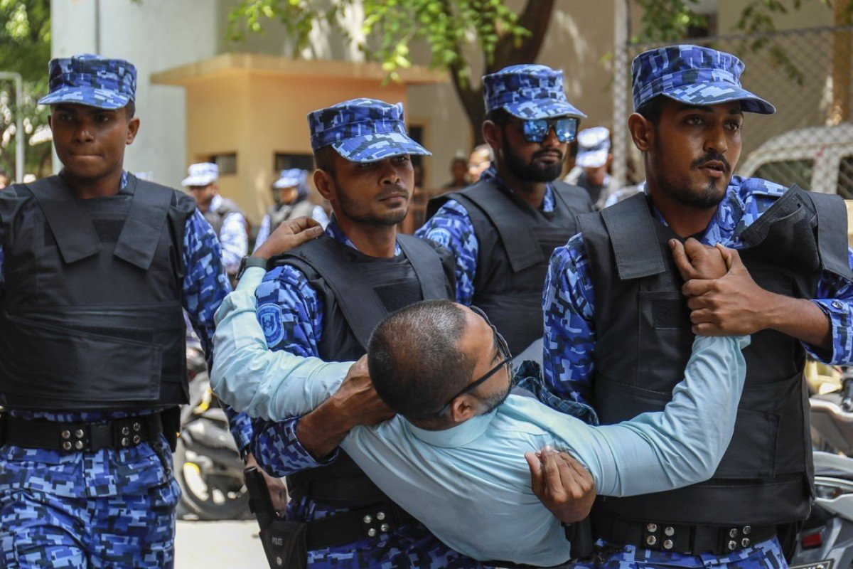 Maldivian police remove an opposition member who tried to enter a Parliament building that closed following the state of emergency. Photo: AP