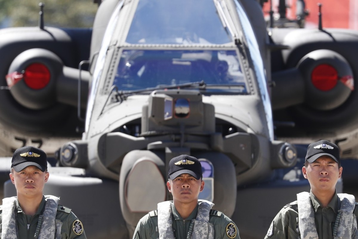 Taiwanese soldiers stand guard in front of US-made Apache attack helicopters on Wednesday. Photo: EPA