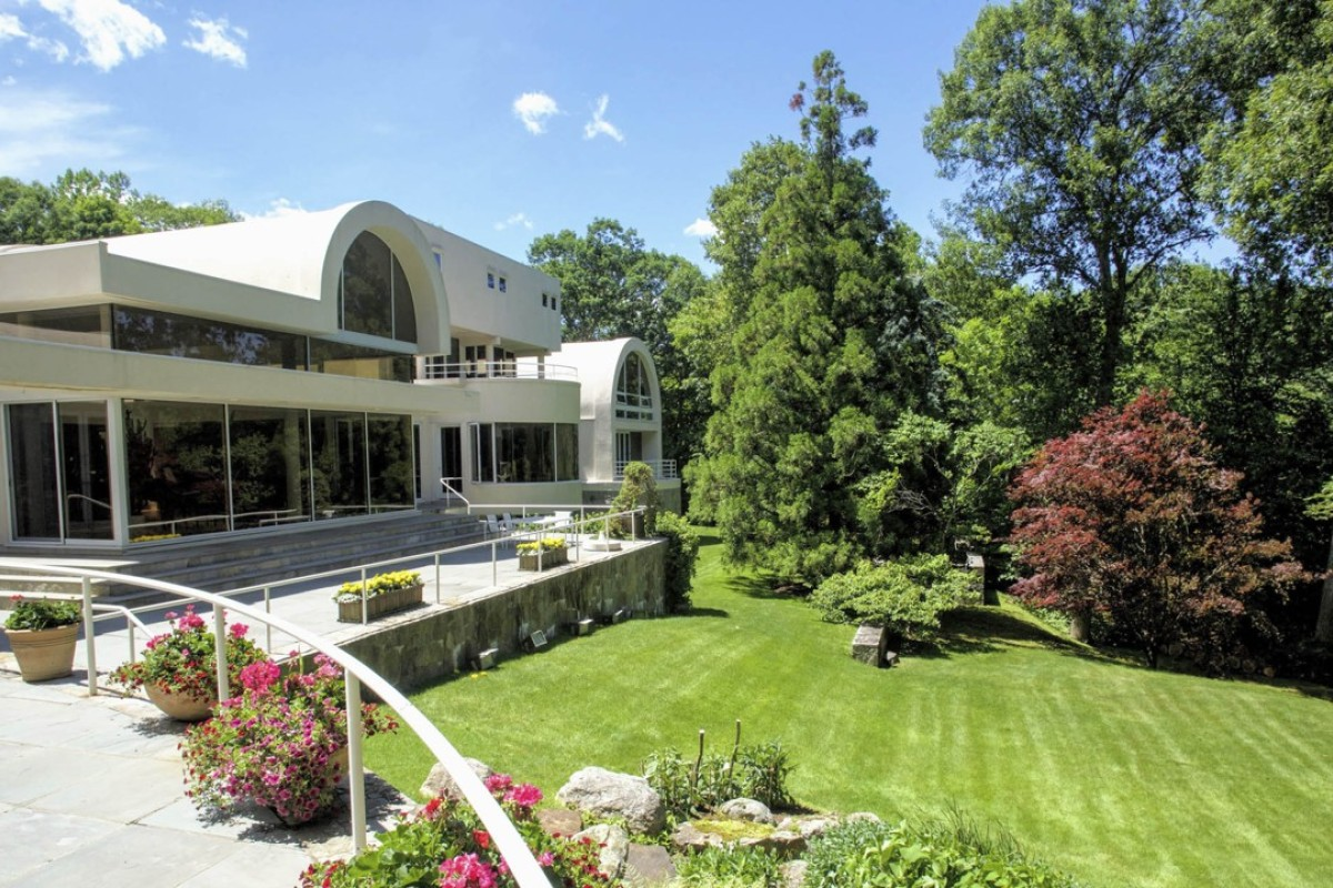 The mansion is constructed over three levels and has terraces overlooking Mallard Lake.
