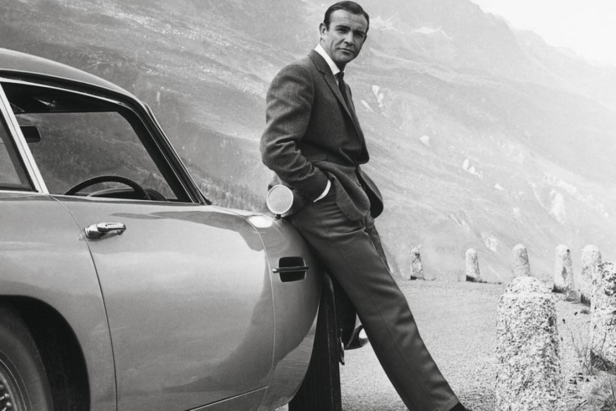 Actor Sean Connery as James Bond, relaxes as he leans against an Aston Martin DB5, which he first drove in the 1964 film, 'Goldfinger'. Source: Aston Martin