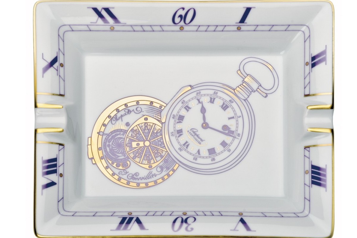Chopard. The porcelain ashtray has a pocket watch theme with the classic timepiece carved in aubergine and gold. There are Roman numerals around the inner edge. Price on request