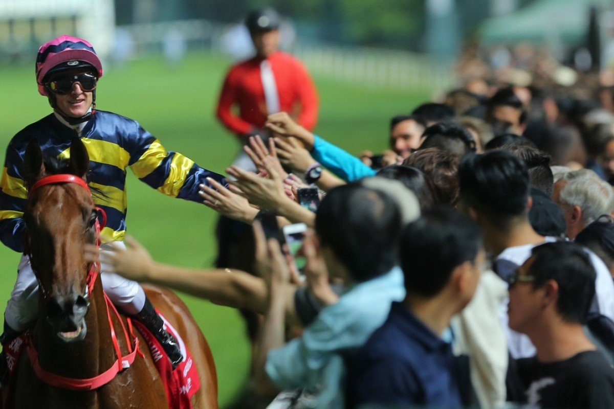Zac Purton celebrates with the Happy Valley crowd after winning on Insayshable. Photos: Kenneth Chan