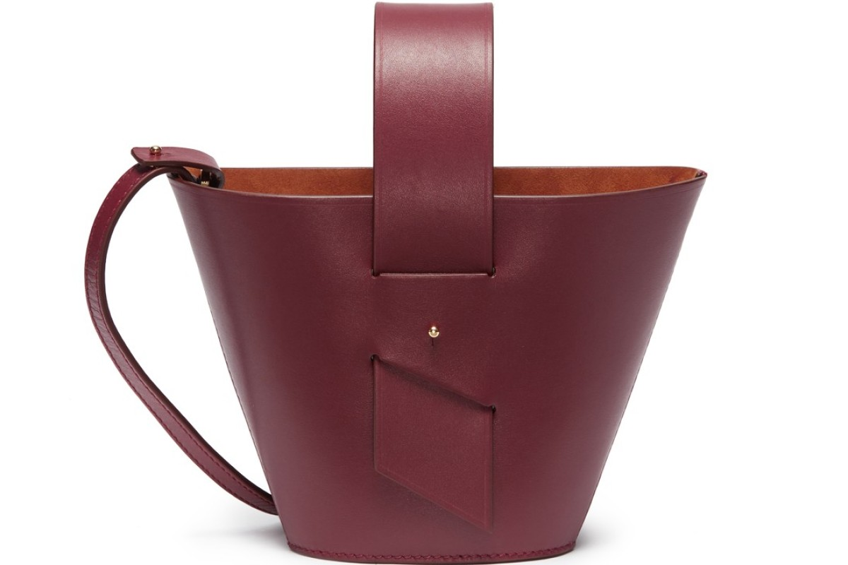 Carolina Santo Domingo. The simple Amphora bucket bag in dark red calfskin leather has a wide handle and a detachable shoulder strap. The bag displays the brand's love of geometric shapes, HK$6,000